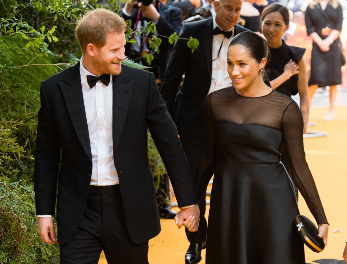 Prince Harry, Duke of Sussex, and Meghan, Duchess of Sussex, holding hands on the red carpet at the 'Lion King' European Premiere in 2019 in London