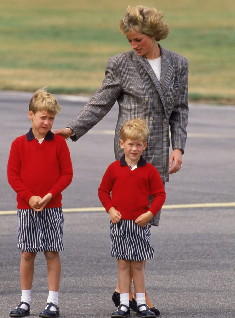Princess Diana wearing a Mardi suit as she arrives at Aberdeen airport with her sons, William and Harry, both dressed in red sweaters and striped shorts