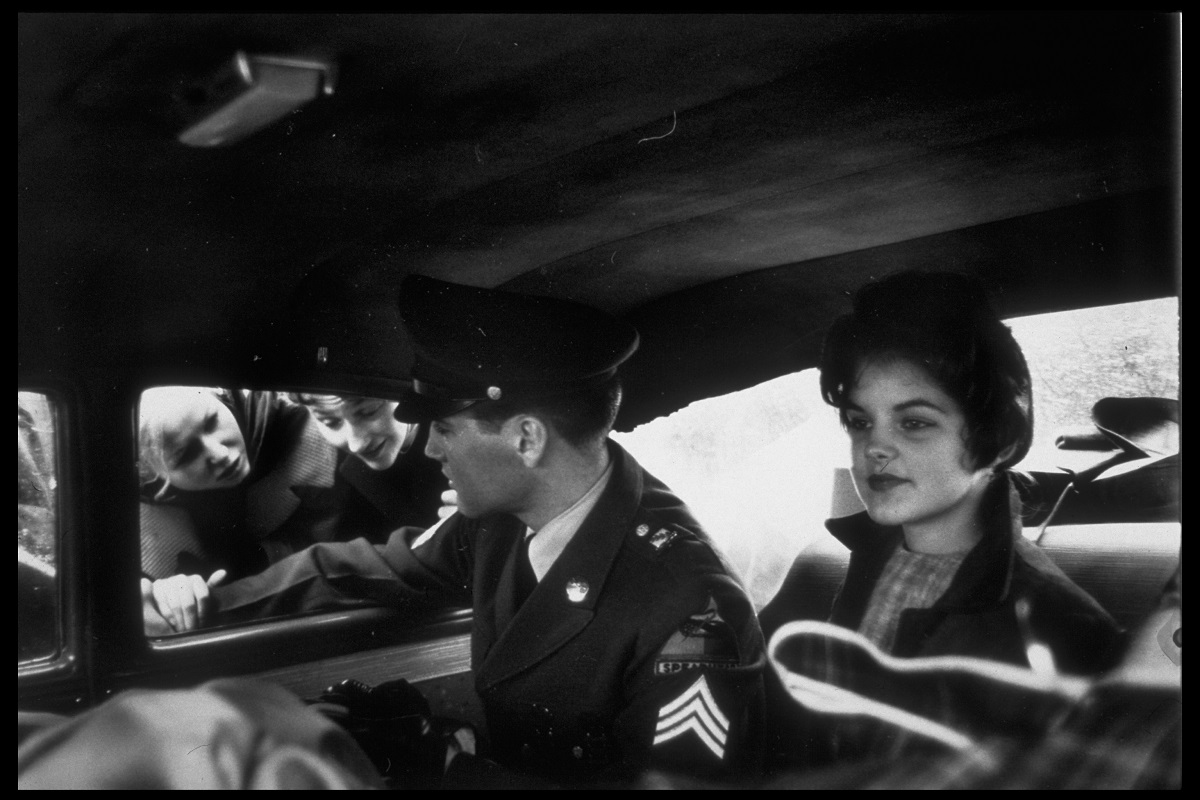 Elvis Presley wearing his military uniform while chatting with fans through the window of a car. A young Priscilla Beaulieu, then his girlfriend, is seated next to him.