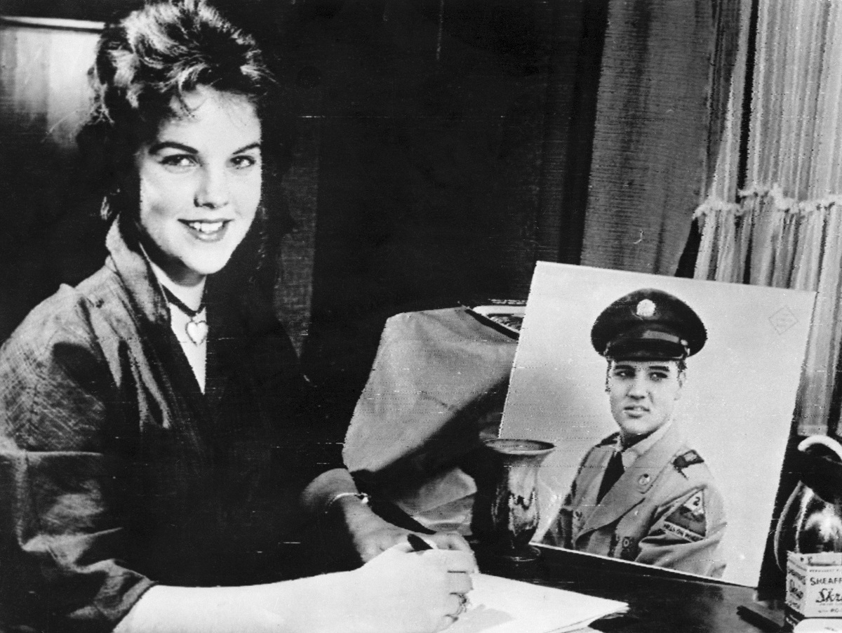 Sixteen year old Priscilla Beaulieu sits before a portrait of a uniformed Elvis Presley as she writes the singer and film star a letter. Beaulieu, the daughter of an Air Force Captain, had dated Presley during the six weeks prior to his departure from Germany for his discharge from the United States Army on March 3, 1960.