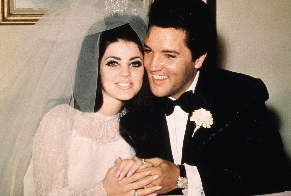 Elvis and Priscilla Presley smiling and holding hands while seated at their reception just after their wedding on May 1, 1967