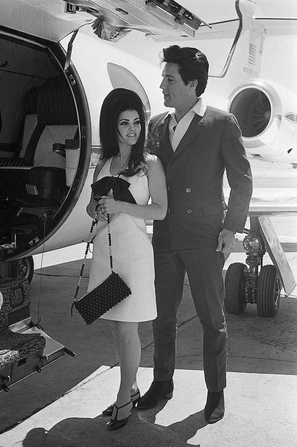 Elvis Presley and his bride, Priscilla Ann Beaulieu smile happily as they prepare to board a chartered jet airplane after their marriage at the Aladdin Hotel in 1967