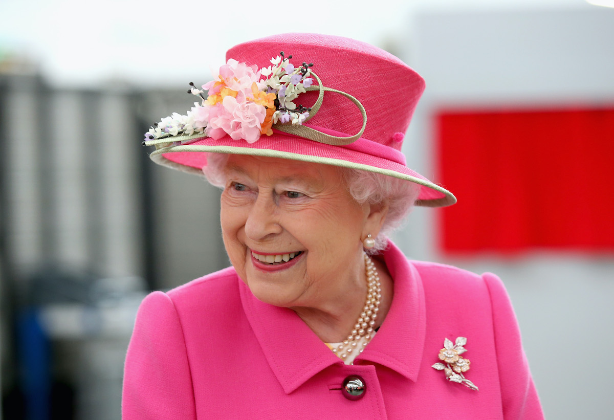 Queen Elizabeth II smiles wearing a pink hat and suit  at a royal engagement in Windsor, England
