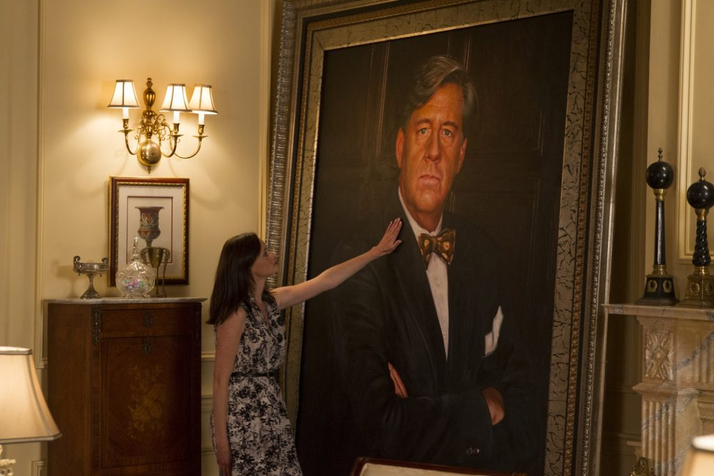 Alexis Bledel as Rory Gilmore stands next to a portrait of Ed Herrmann as Richard Gilmore in 'Gilmore GIrls: A Year in the Life'