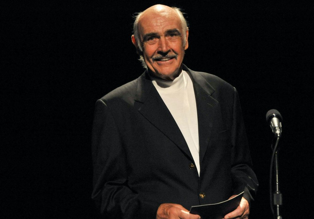 Sean Connery smiling behind a microphone in front of a black background