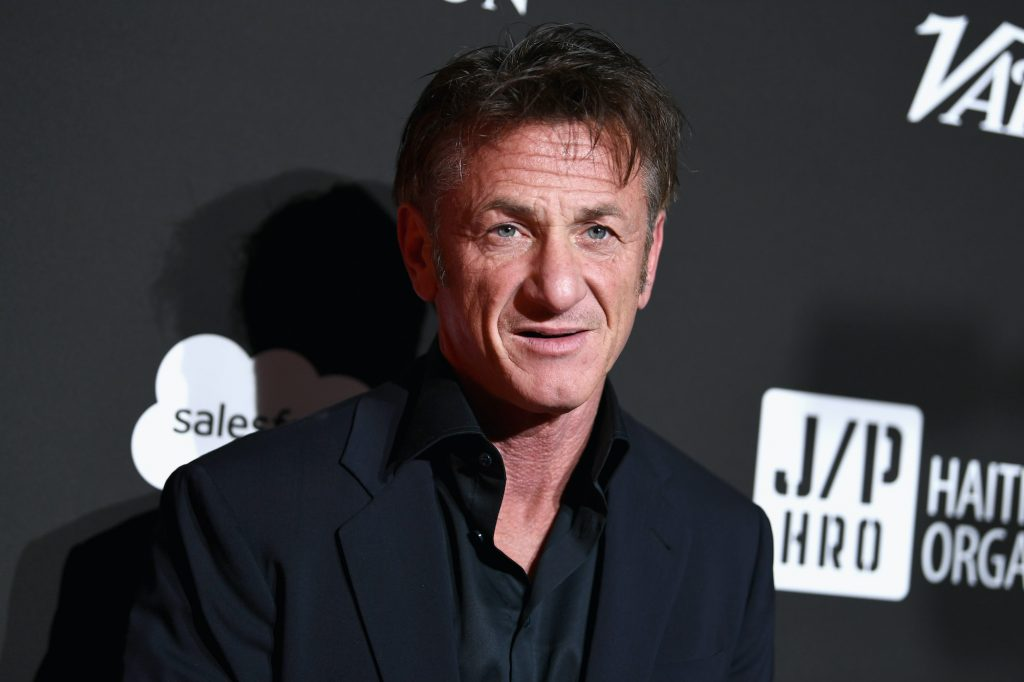 Sean Penn standing in front of a gray background