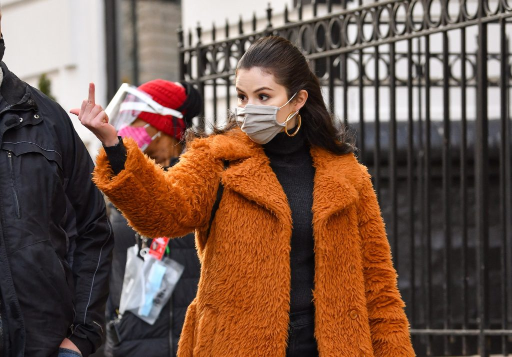 Selena Gomez wearing a mask, holding up her middle finger to the left