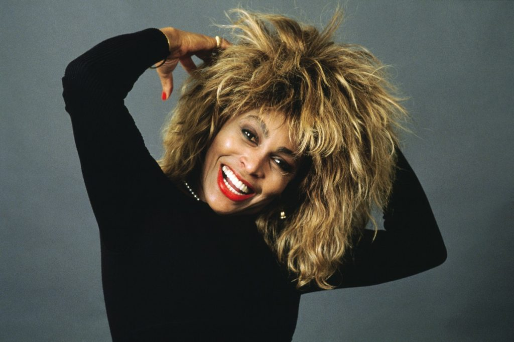 Singer Tina Turner smiling for portrait wearing a black top and pearl necklace