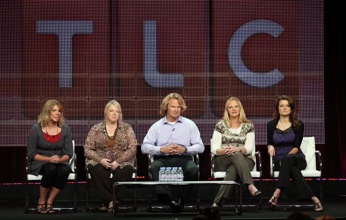 Meri, Janelle, Kody, Christine, and Robyn Brown of 'Sister Wives' sitting on a panel in front of a giant TLC logo during the Summer TCA Press Tour in 2010