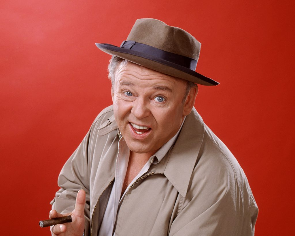Studio portrait of Carroll O'Connor wearing a brown hat with a beige jacket and holding a cigar