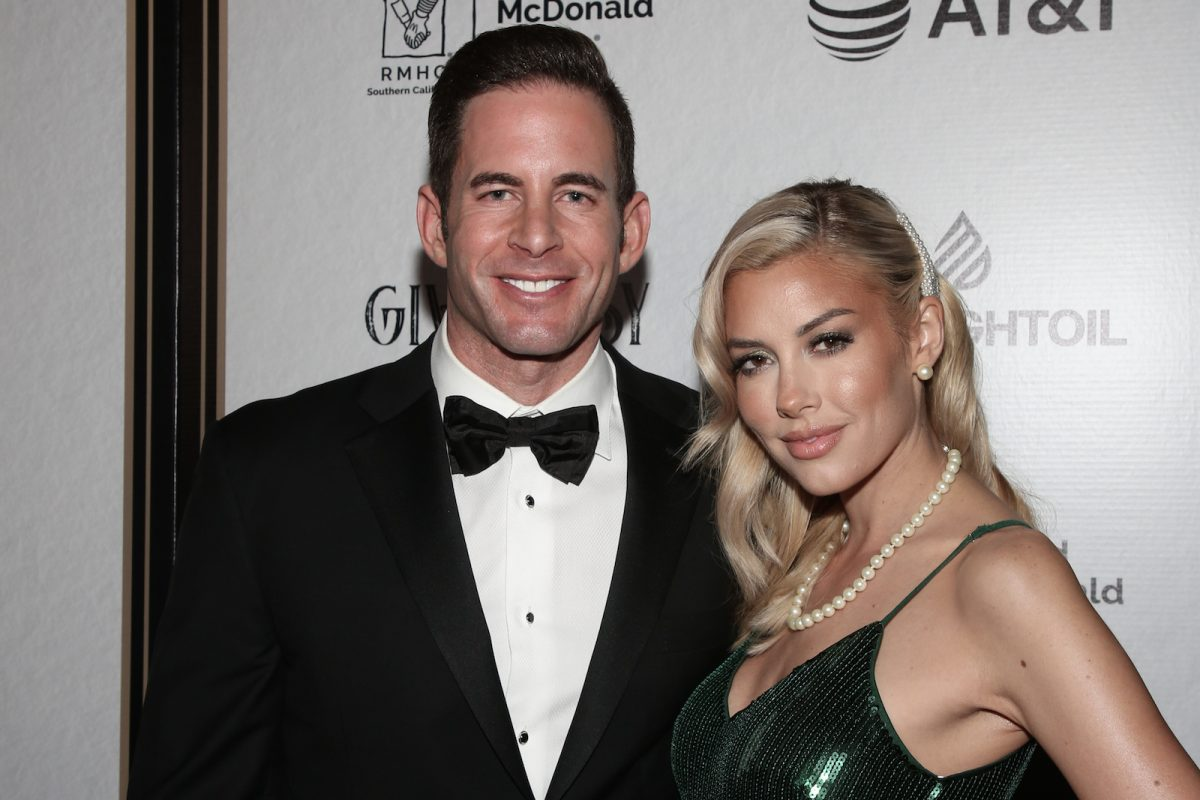 Tarek El Moussa from 'Flip or Flop' in a tuxedo and Heather Rae Young from 'Selling Sunset' in a green sequin dress standing together and smiling at an event. El Moussa and Young might both appear on 'Selling Sunset' Season 4