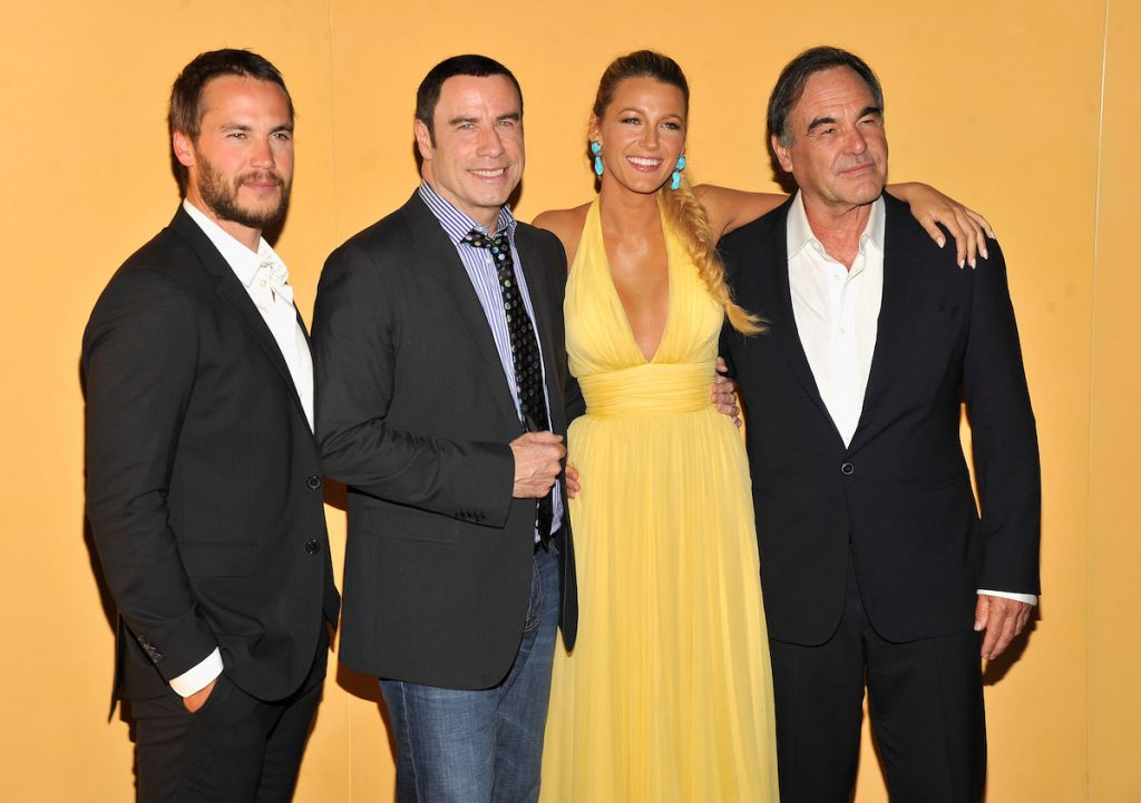 Taylor Kitsch, John Travolta, Blake Lively, and Oliver Stone smile as they pose together for cameras at the New York City premiere of 'Savages' in 2012