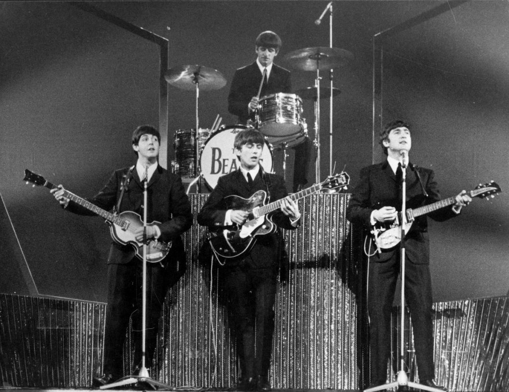 The Beatles perform at the London Palladium with Ringo Starr on drums, rear, and  (L to R): Paul McCartney, George Harrison, and John Lennon on bass guitar, lead guitar, and rhythm guitar, respectively