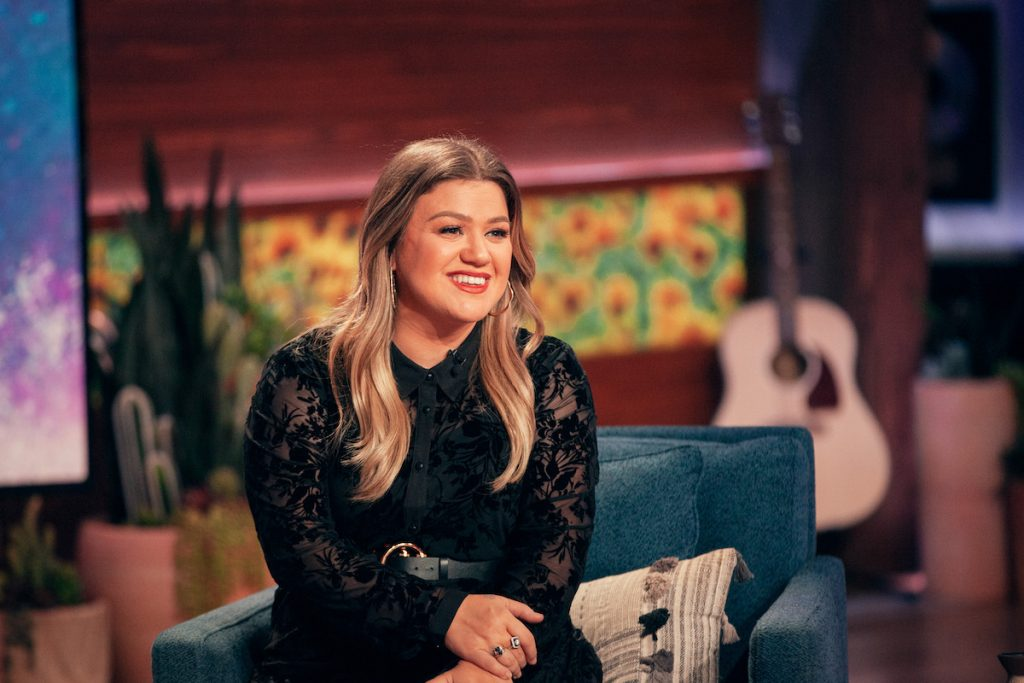 Kelly Clarkson sits on the couch smiling on 'The Kelly Clarkson Show'