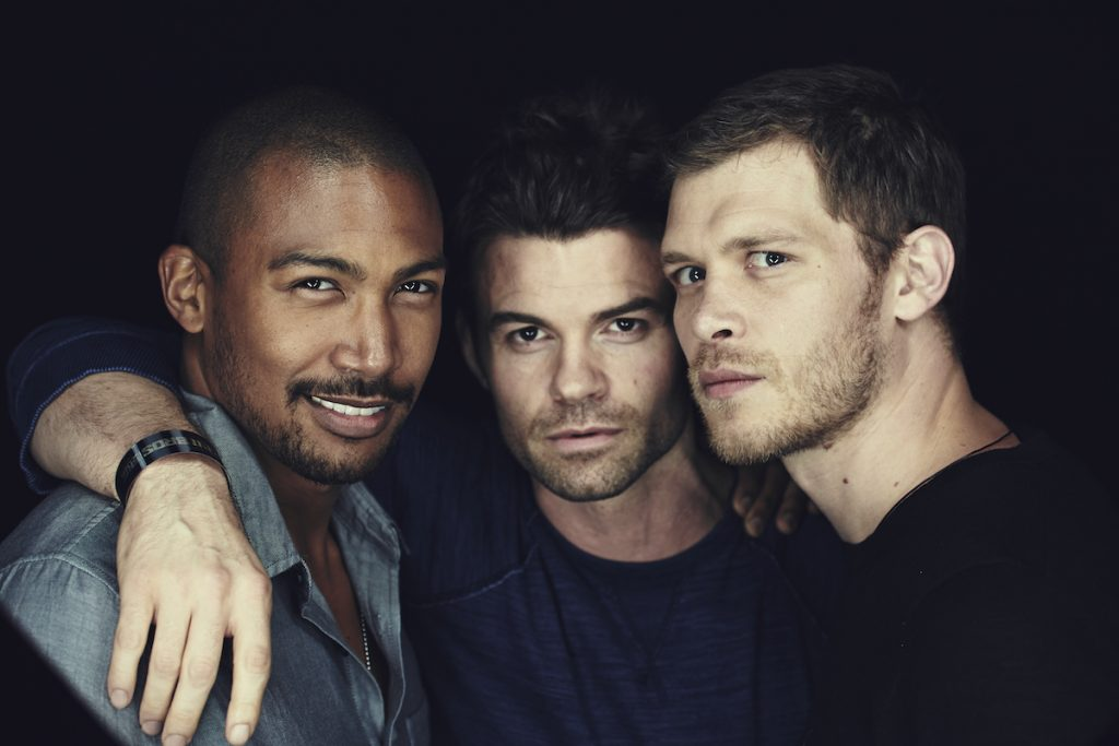 Charles Michael Davis, Daniel Gillies, and Joseph Morgan of 'The Originals' pose side-by-side in front of a black background