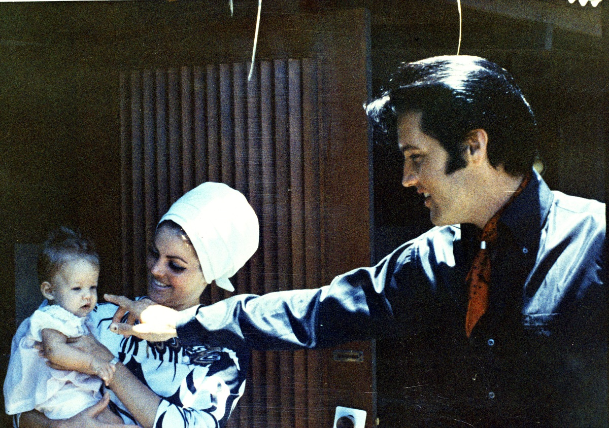 Elvis Presley and Priscilla Presley smiling with baby Lisa Marie Presley in a candid shot