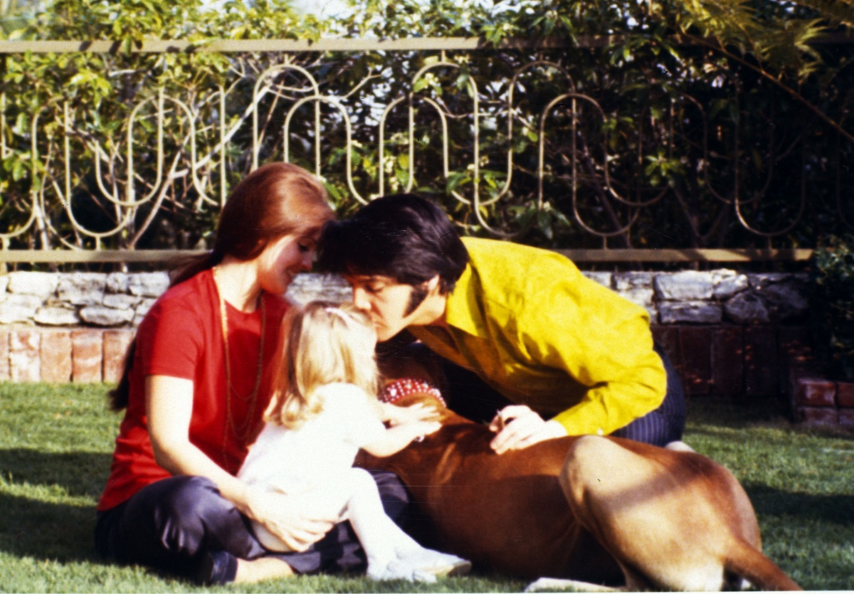 Elvis Presley leaning over to kiss Lisa Marie Presley as a child while Priscilla Presley looks on. The Presleys are sitting on the lawn. Lisa Marie is petting a dog.