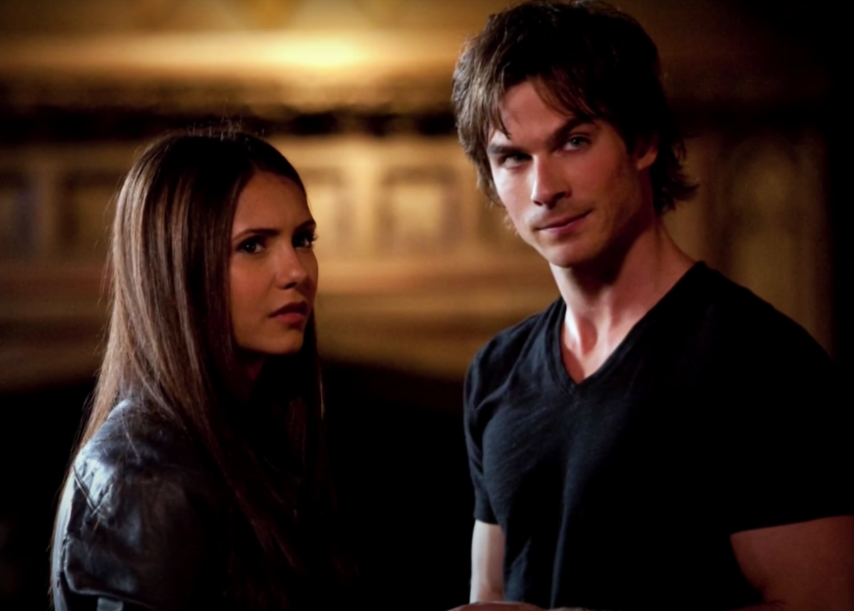 Elena and Damon in 'The Vampire Diaries' stand in front of a fireplace