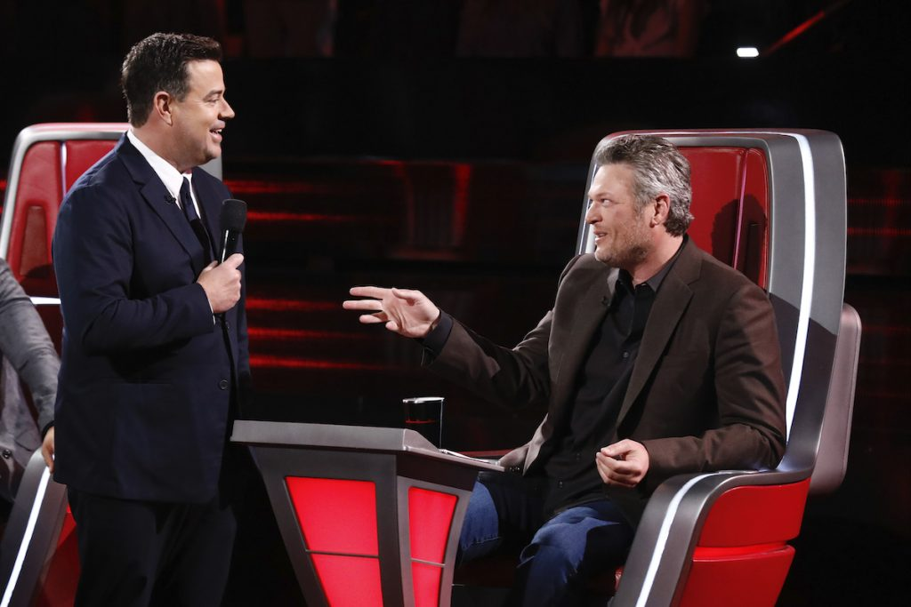 Carson Daly stands in front of Blake Shelton who is sitting on set of 'The Voice'