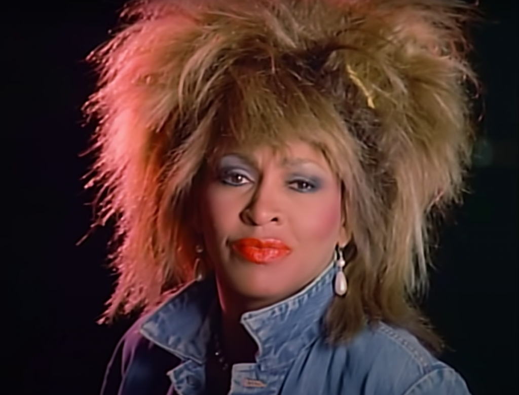 Tina Turner with her hair teased high wearing a blue denim jacket and bright red lipstick in the 'What's Love Got to Do With It' music video