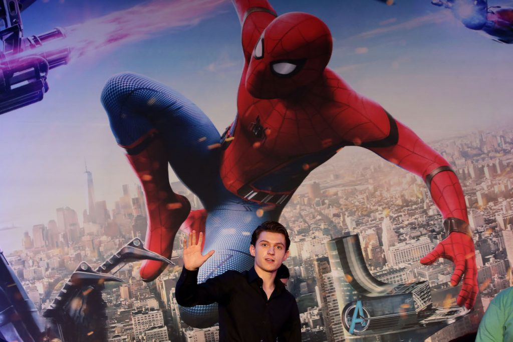 Tom Holland waves in front of Spider-Man poster