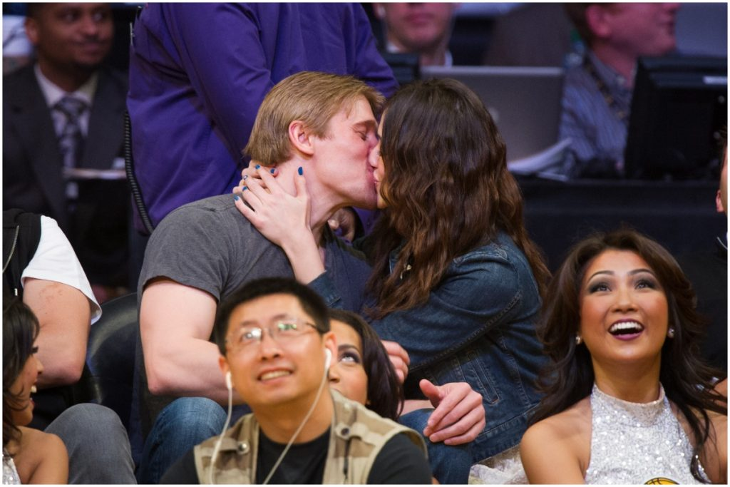 Tyler Jacob Moore and Emmy Rossum kissing at a basketball game.