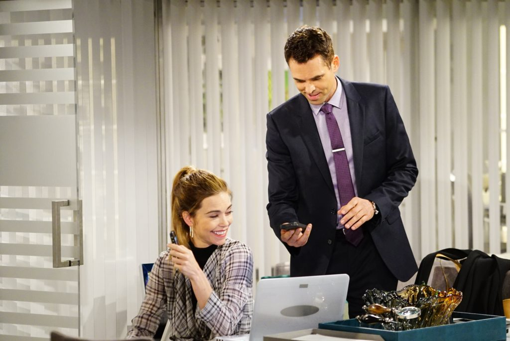(L-R) Amelia Heinle as Victoria Newman and Jason Thompson as Billy Abbott, laughing gathered around a desk