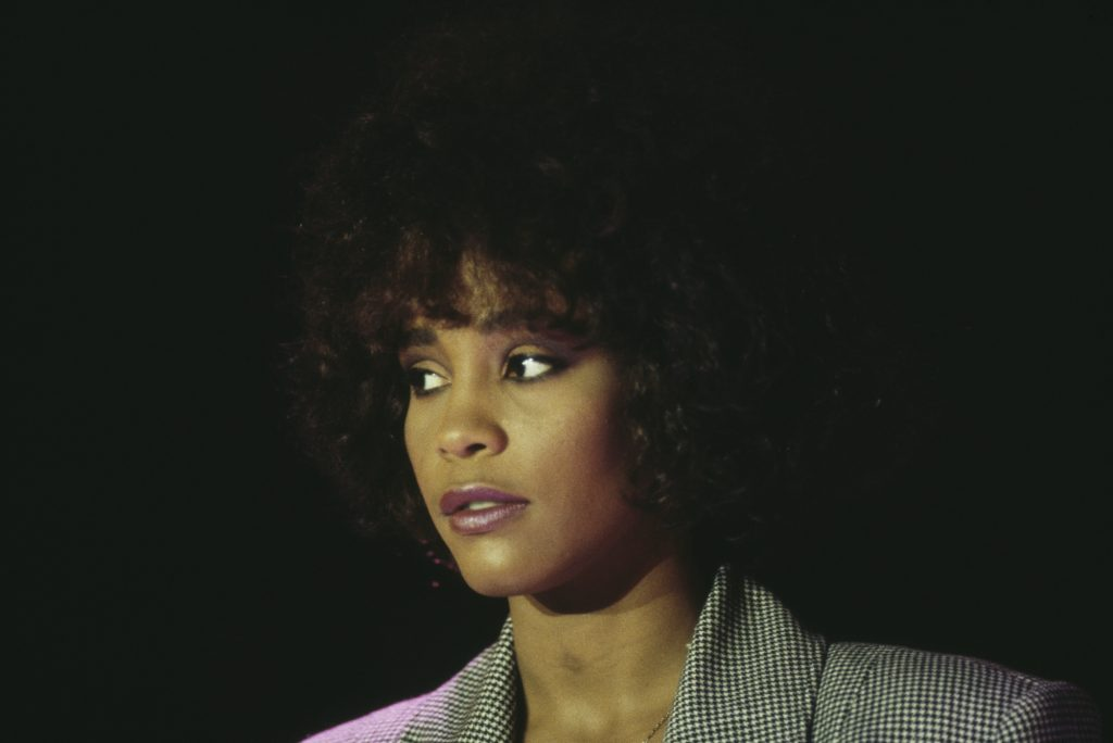 Whitney Houston smiling in front of a black background