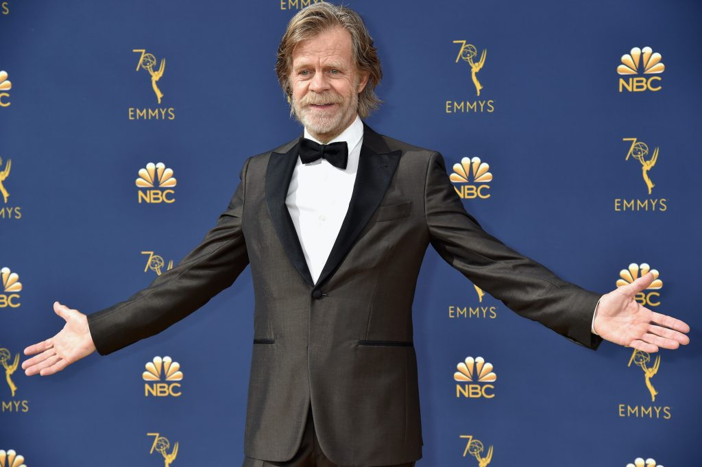 William H. Macy smiling, arms outstretched, in front of a blue background