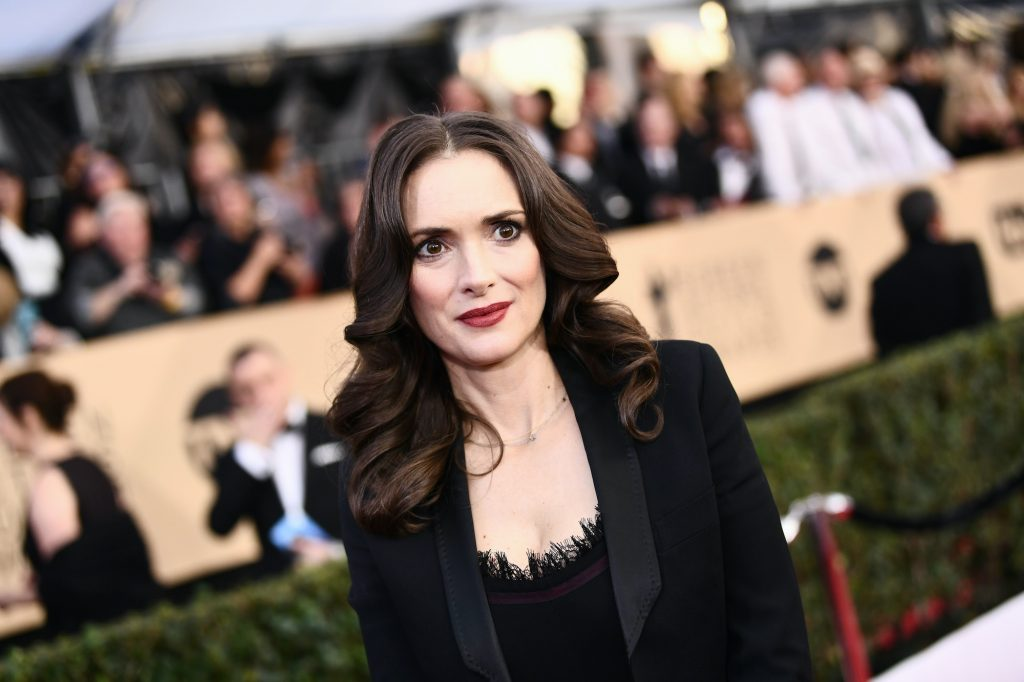 Winona Ryder smiling in front of a blurred crowd