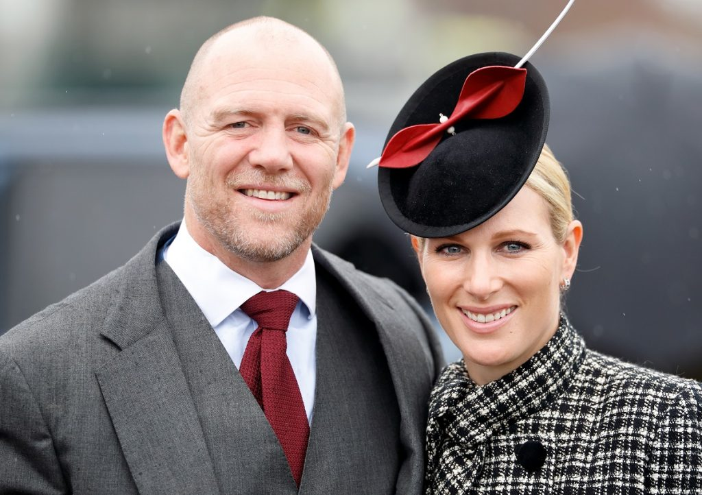 Zara Tindall in a black-white fascinator and Mike Tindall in a suit and red tie pose for a photo together whille attending the Cheltenham Festival at Cheltenham Racecourse