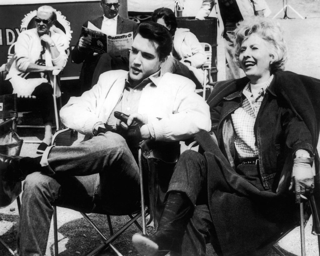 Elvis Presley holding hands with Barbara Stanwyck
