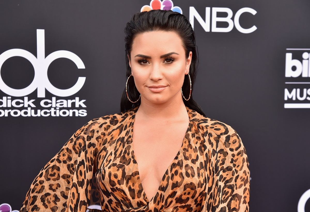 Demi Lovato in a leopard-print dress looking staring straight ahead