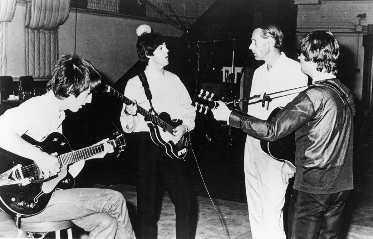 Paul McCartney, standing and holding a bass guitar, looks at George Martin as a seated George Harrison and standing John Lennon play guitar