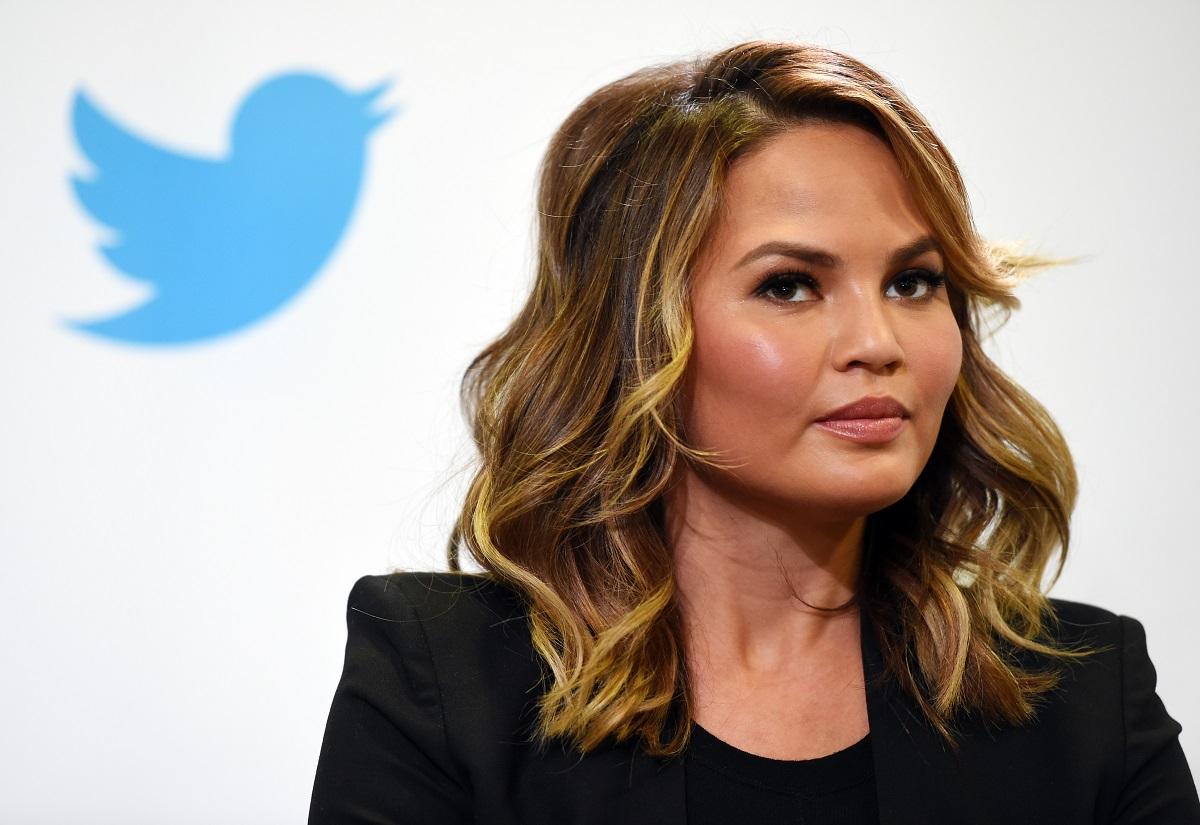 Chrissy Teigen in front of the Twitter logo
