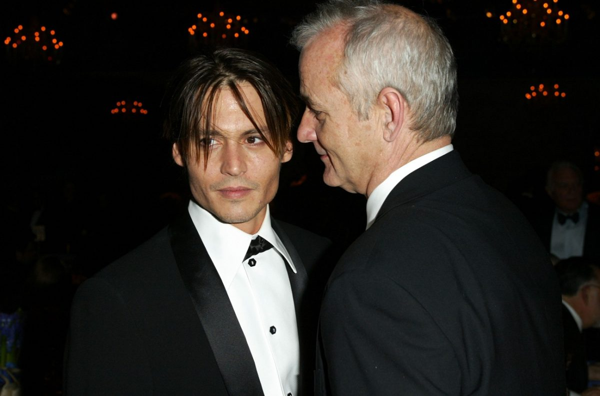 Johnny Depp has a slight smile and looks away as Bill Murray speaks very closely to his left ear