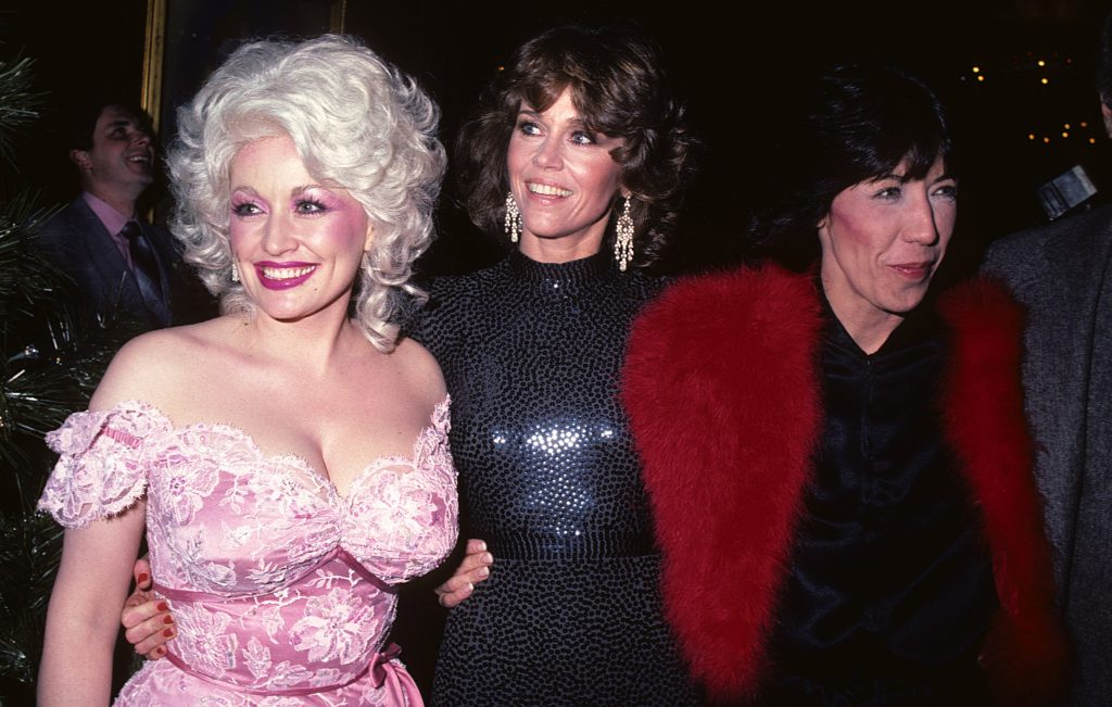 Dolly Parton, Jane Fonda, and Lily Tomlin near other people