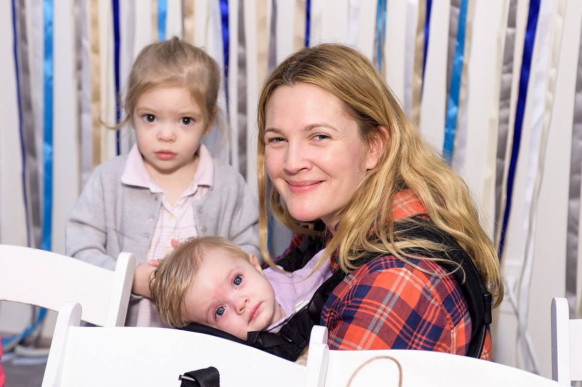 Drew Barrymore holding her daughter, Frankie, while her daughter, Olive, looks at the camera