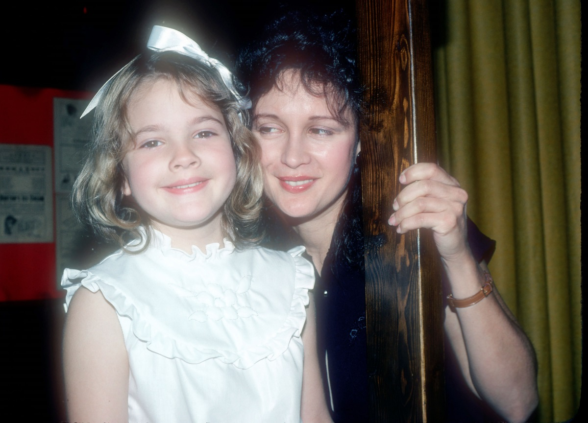 Drew Barrymore as a child in a white dress and bow with her mother, Jaid.