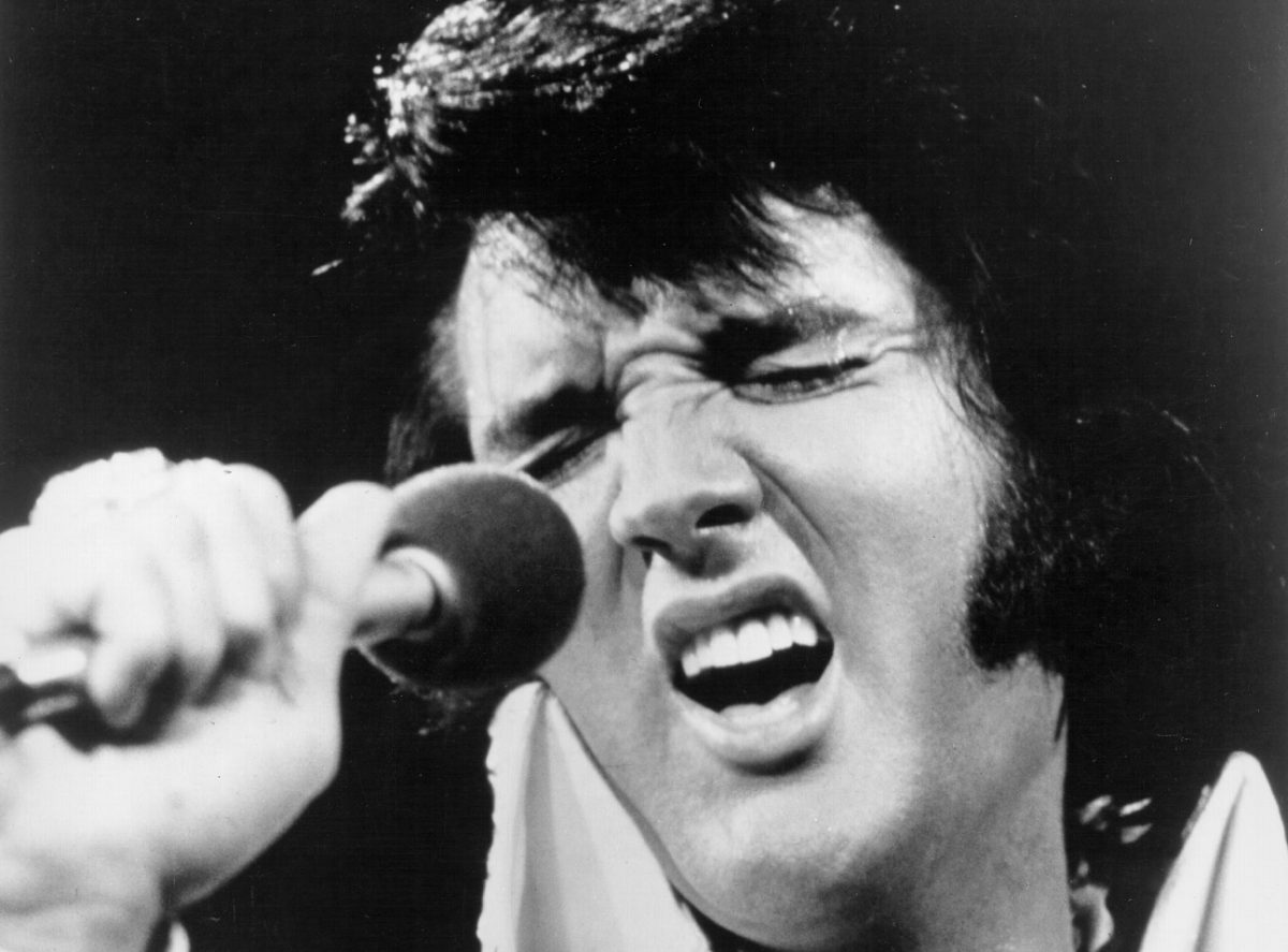 Closeup of Elvis Presley with his eyes closed singing into a microphone