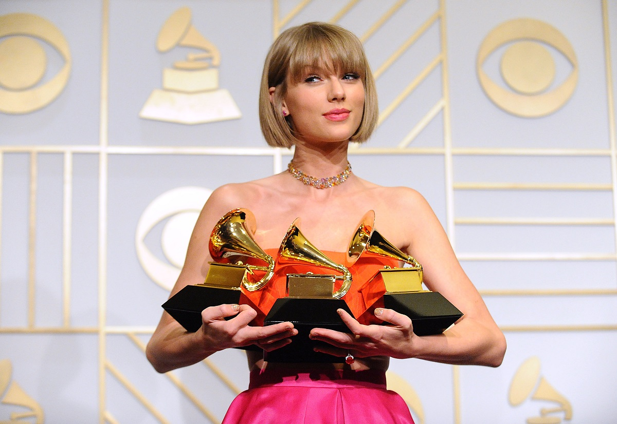 Taylor Swift in a pink dress holding three Grammy Awards