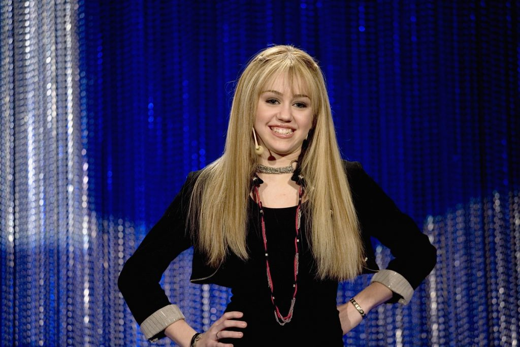 Miley Cyrus in a blonde wig with her hands on her hips