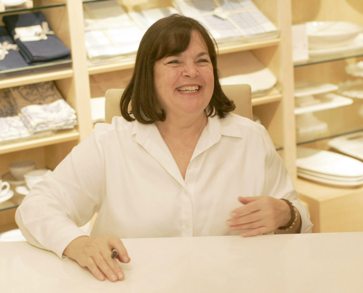 Ina Garten smiles as she sits at a table during a book signing at William Sonoma