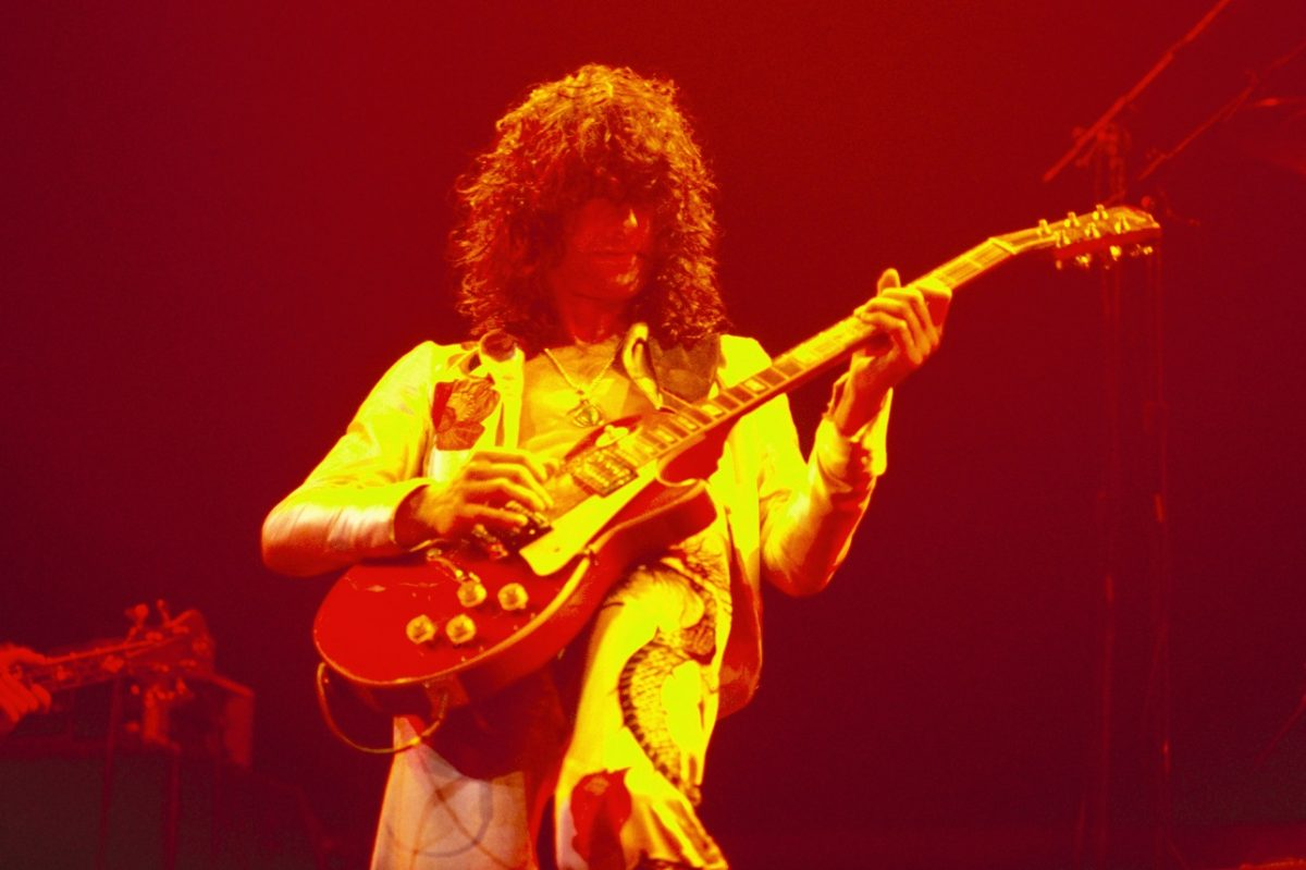 Jimmy Page playing guitar bathed in orange light on stage