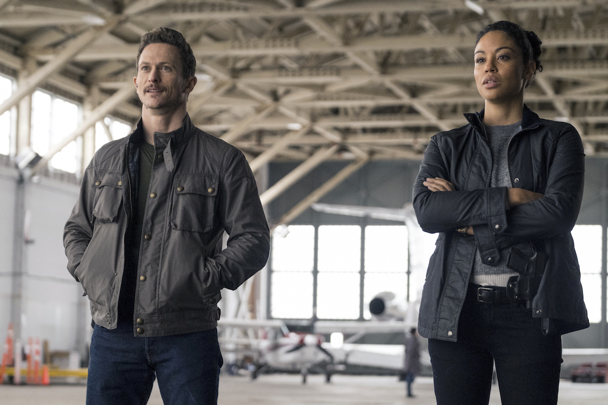 Bryan and Finola standing next to each other in an airplane hanger in Debris series premiere