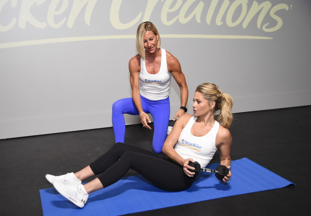 Candace Cameron Bure works out with a weight on a mat with the help of trainer Kira Stokes