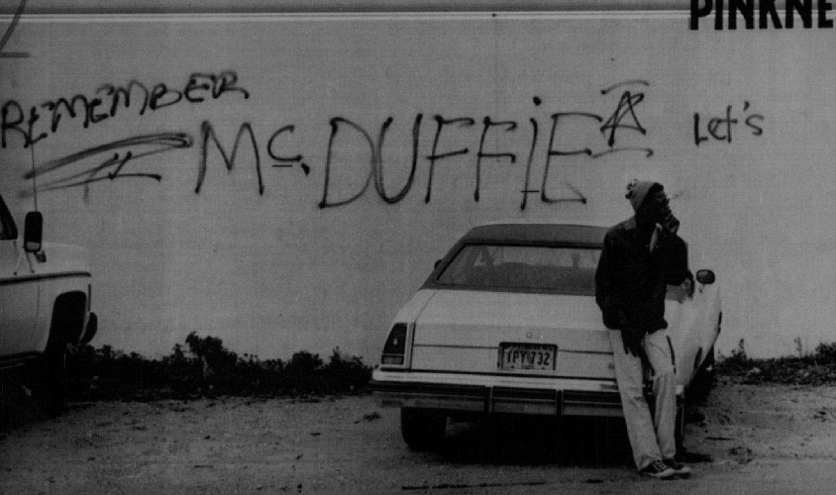 A young Black man stands in front of a graffiti-covered wall in Miami, a reminder of the riots set off when policemen were acquitted for the murder of Arthur McDuffie