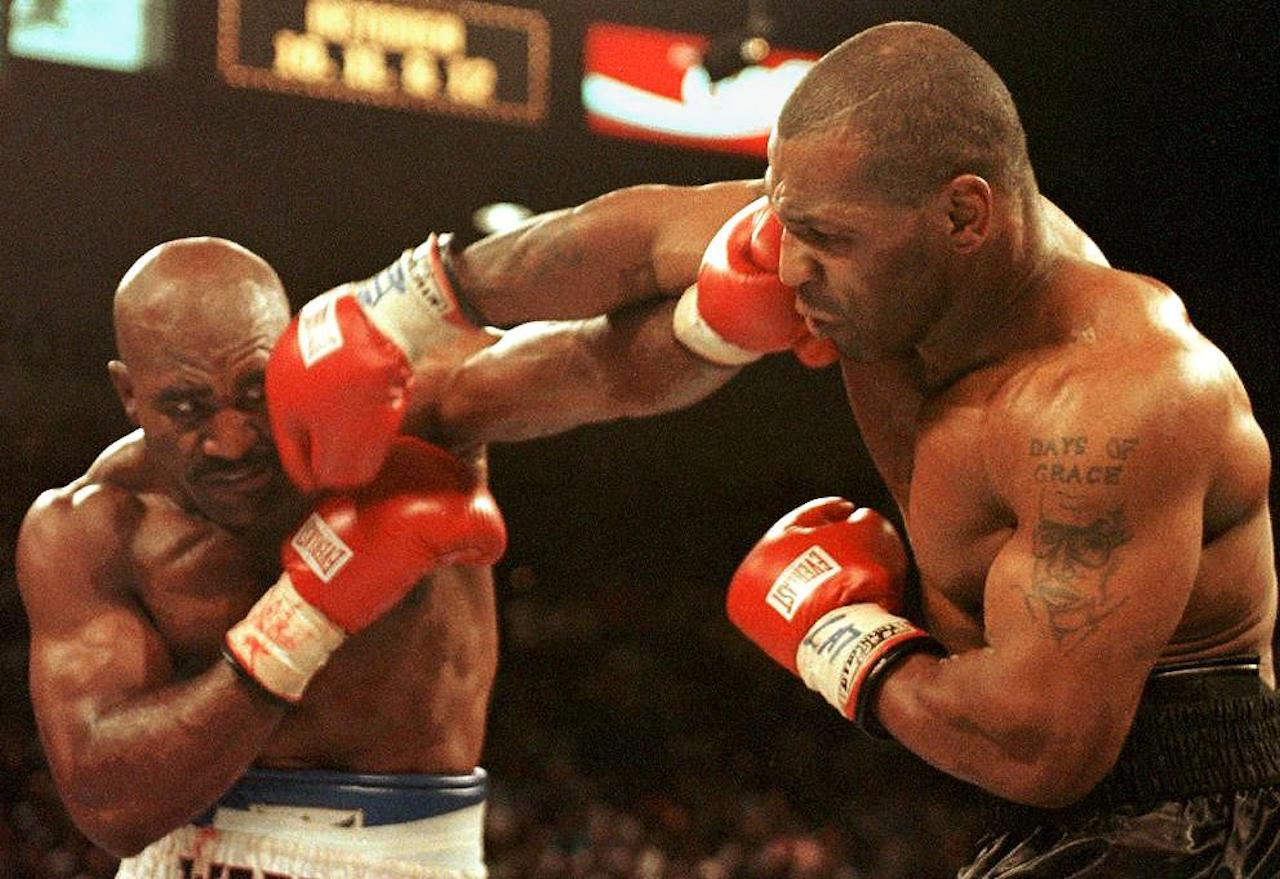 Evander Holyfield (L) and Mike Tyson (R) trade punches 28 June in their WBA heavyweight Cchampionship fight