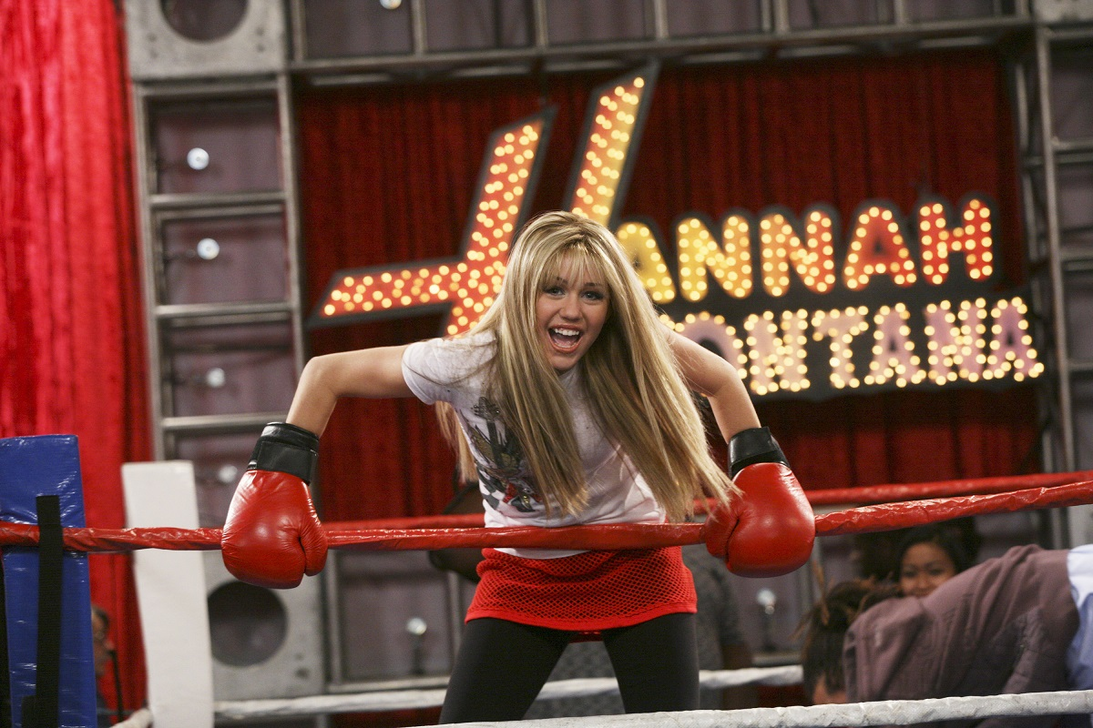 Miley Cyrus in a blonde wig wearing boxing gloves in front of a 'Hannah Montana' sign