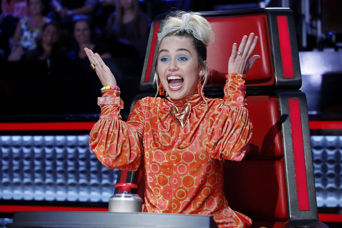 Miley Cyrus in a red chair on 'The Voice' with her hands in the air